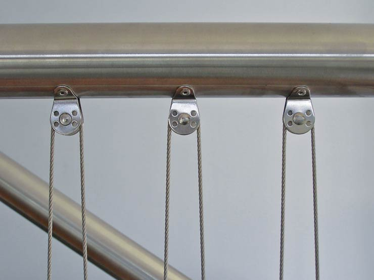 3 rounded stainless steel pulleys attached to a handrail.